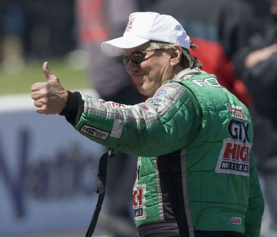 Funny Car driver John Force gives a thumbs up. Photo: James Nielsen, Chronicle