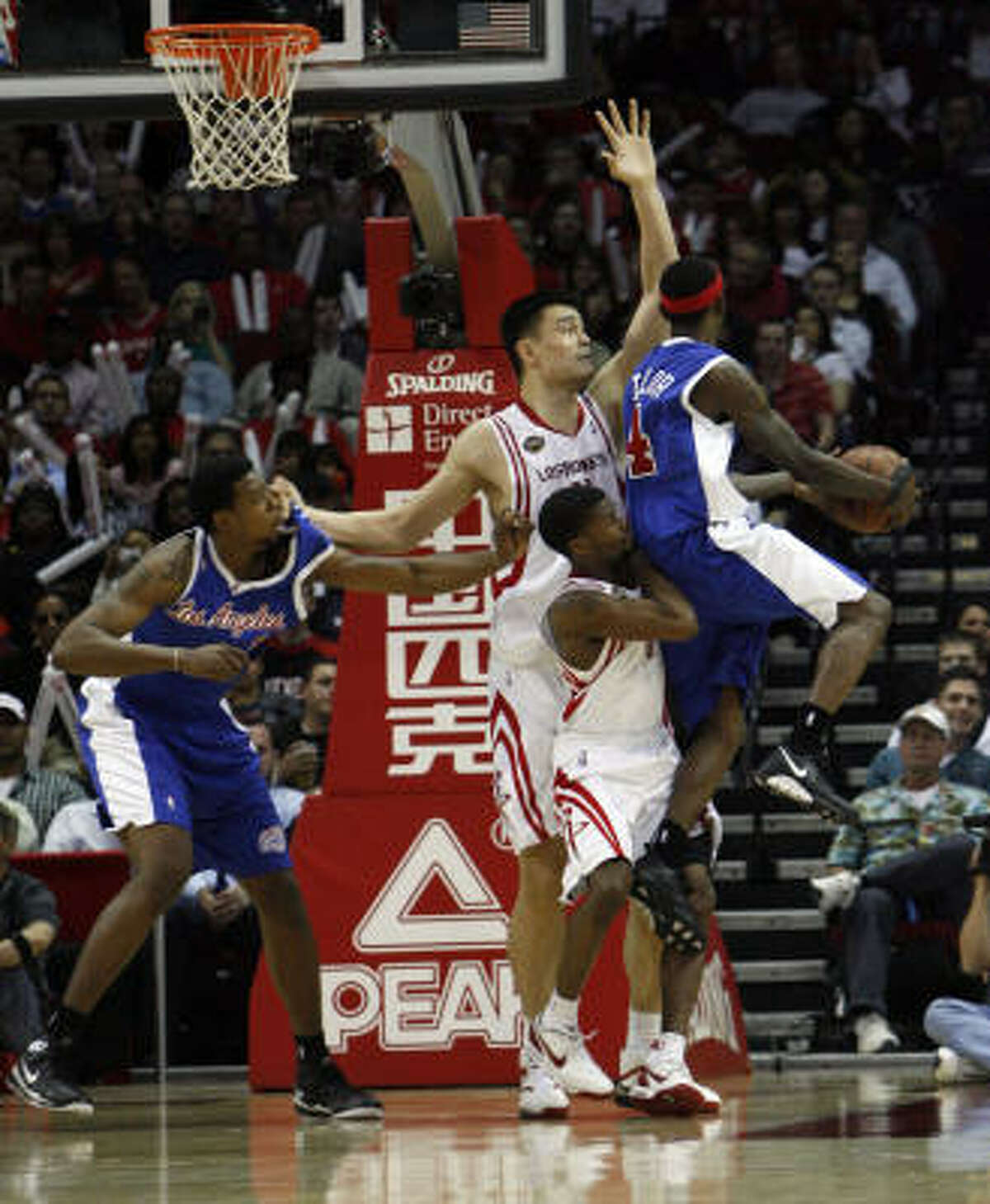 Yao Ming, (#11) and Aaron Brooks block the paint as Clippers guard Mike Taylor puts up an akward shot in the third quarter.
