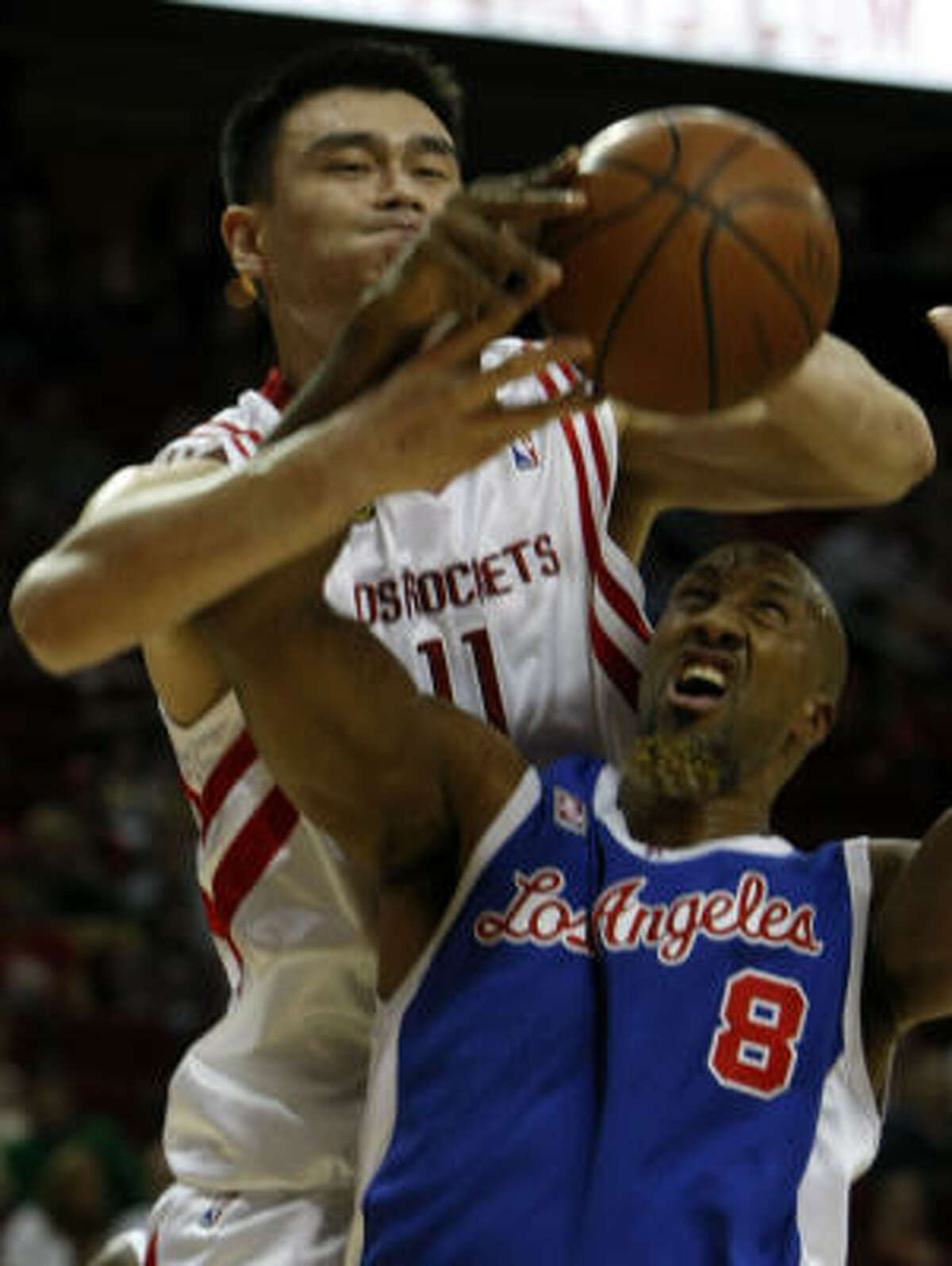 Yao Ming, top, battles Clippers forward Brian Skinner for a loose ball in the second quarter.