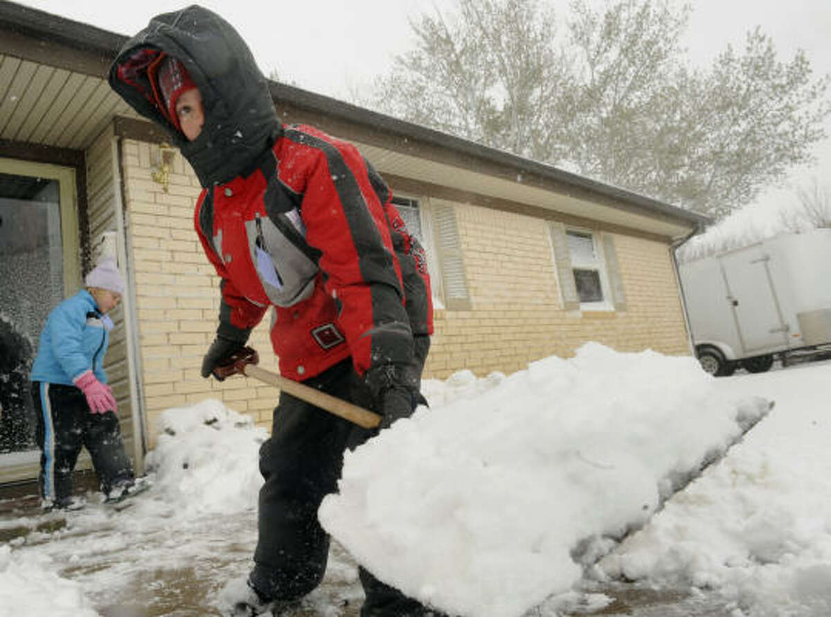 Jocelyn Fehr, 7, left, and Austin Fehr, 9, shovel snow in front of their home Friday.