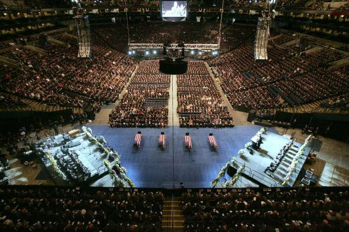 The flag draped caskets of Oakland Police Officers Sgt. Mark Dunakin, 40; John Hege, 41; Sgt. Ervin Romans, 43; and Sgt. Daniel Sakai, 35, are seen in the Oracle Arena in Oakland, Calif. Thousands of mourners have gathered with the families of four slain Oakland police officers for a joint funeral that drew law enforcement from around the world.