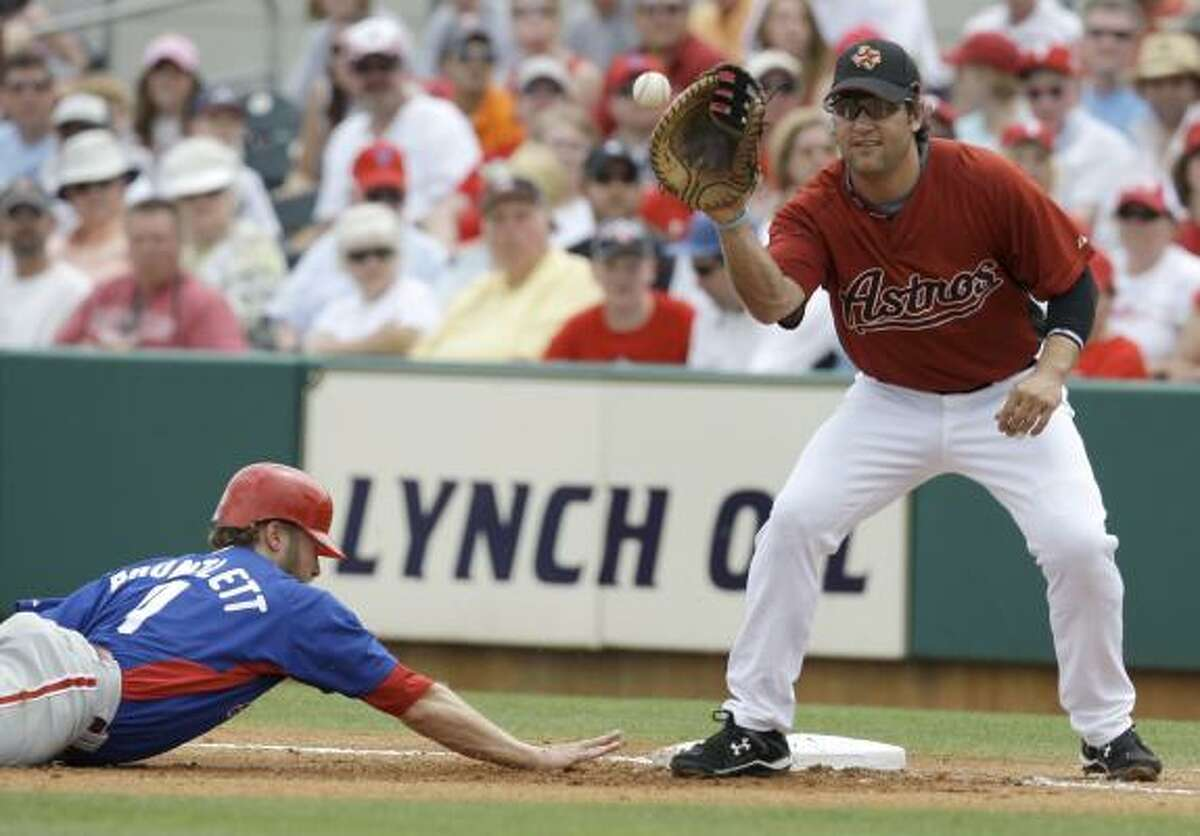 Phillies infielder Eric Bruntlett, a former Astro, dives safely back to first base as Astros first baseman Lance Berkman waits for Roy Oswalt's pickoff throw during the first inning.