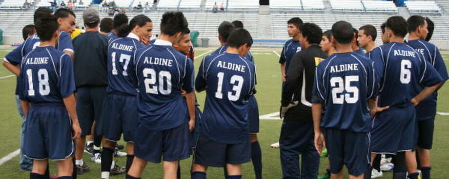 Aldine soccer players get a last-minute pep talk from their coach. Photo: Gerald James, For The Chronicle
