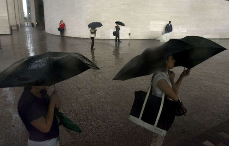 Pedestrians wait for a bus next to Jones Hall as as stormy weather doused downtown in Houston. Photo: Johnny Hanson, Chronicle