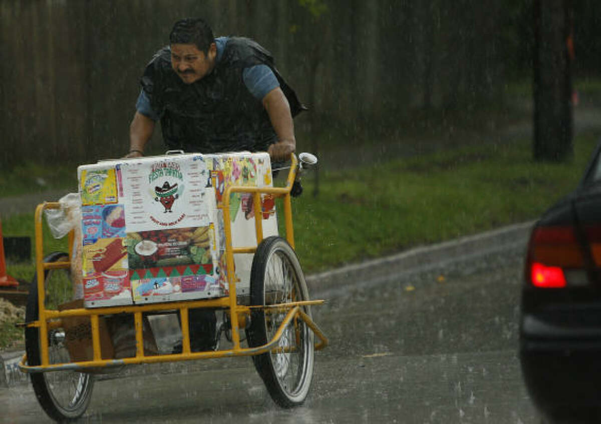 Ice cream seller Jose Morales pedals along 20th St. in the Heights in attempts to find a shelter from the pouring rain in Houston.