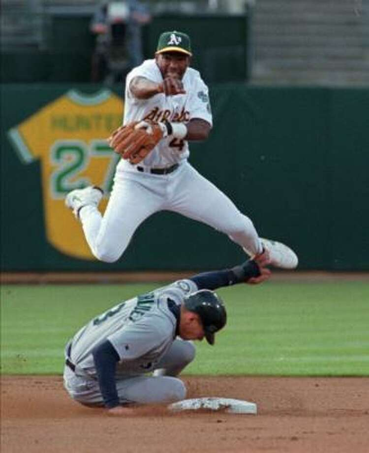 1998: Miguel Tejada, seen here leaping over a young Alex Rodriguez (also in the news this week), played his first full season with the 1998 Athletics. Photo: GEORGE NIKITIN, AP