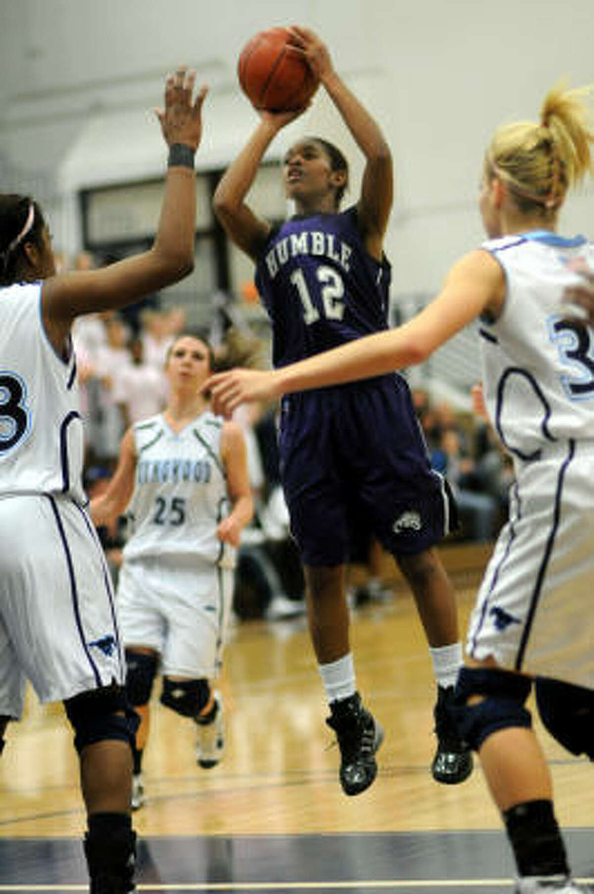 Humble's Jessica Hines shoots between Kingwood's Michelle Price, left, and Ashley Wiens.
