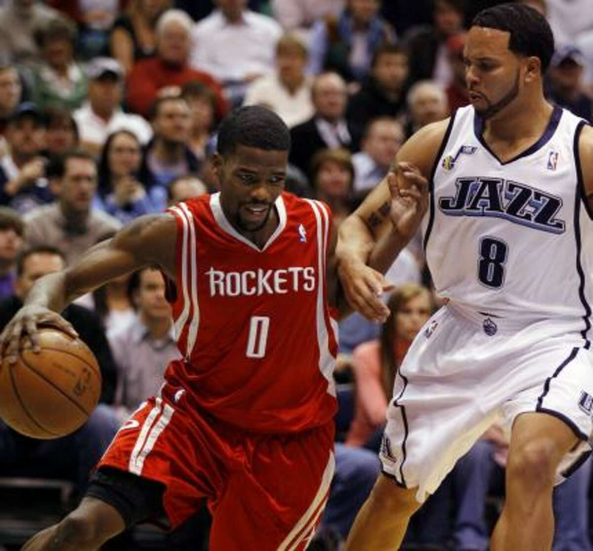 Houston Rockets guard Aaron Brooks drives around Utah Jazz guard Deron Williams during the first half.