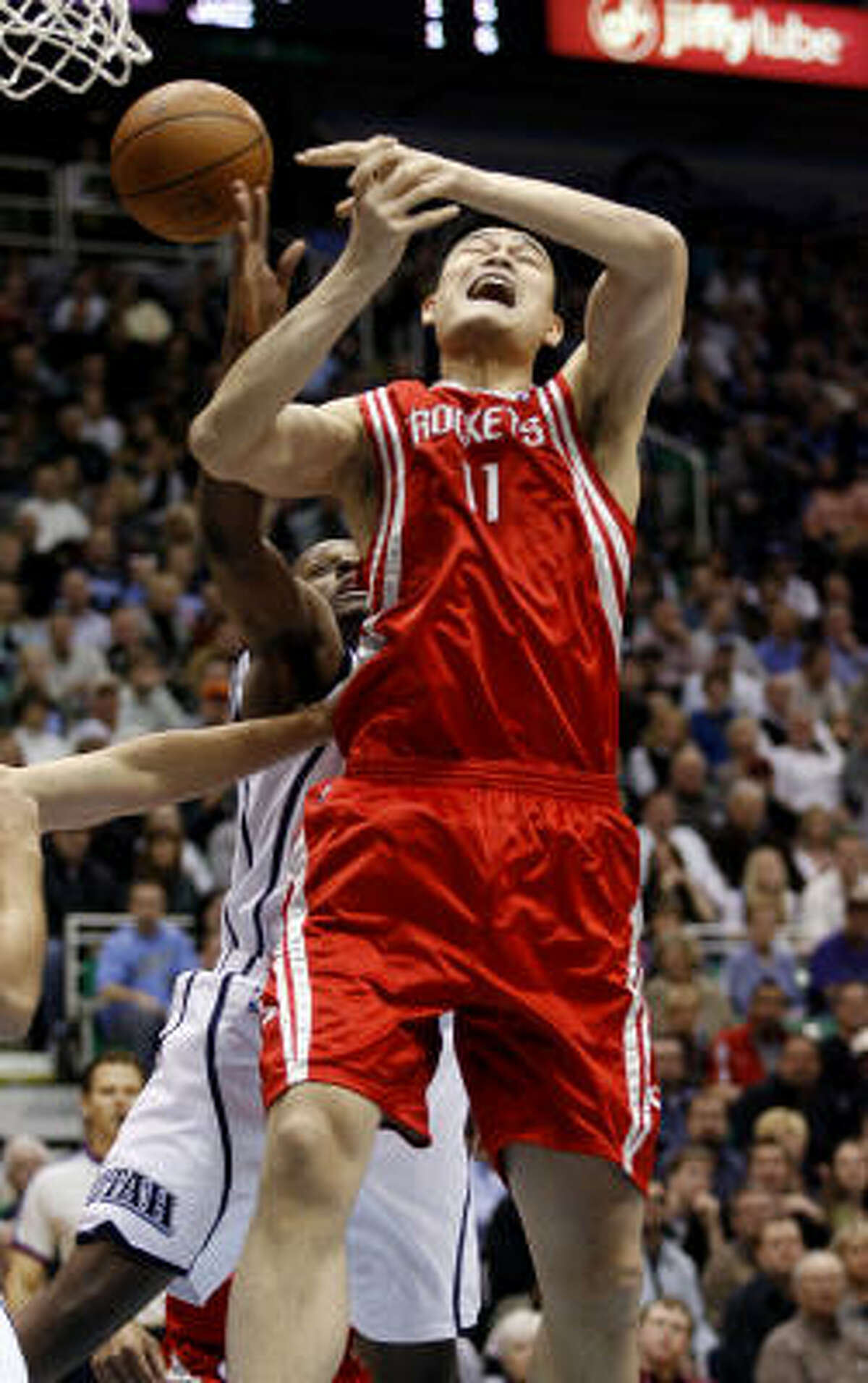 Houston Rockets center Yao Ming loses control of the ball under the basket while being guarded by Utah Jazz forward C.J. Miles.