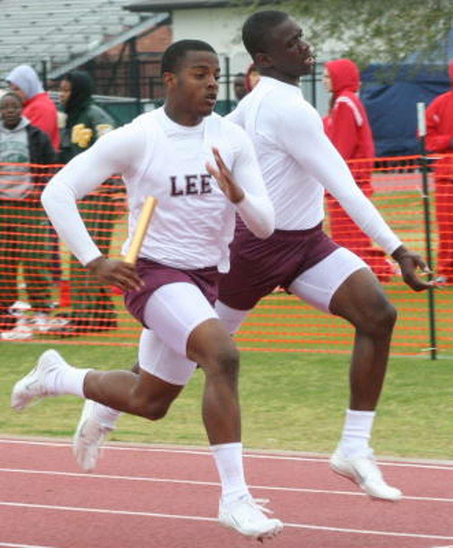 Baytown Lee's Dandrick Jackson (left) gets the baton from his teammate.