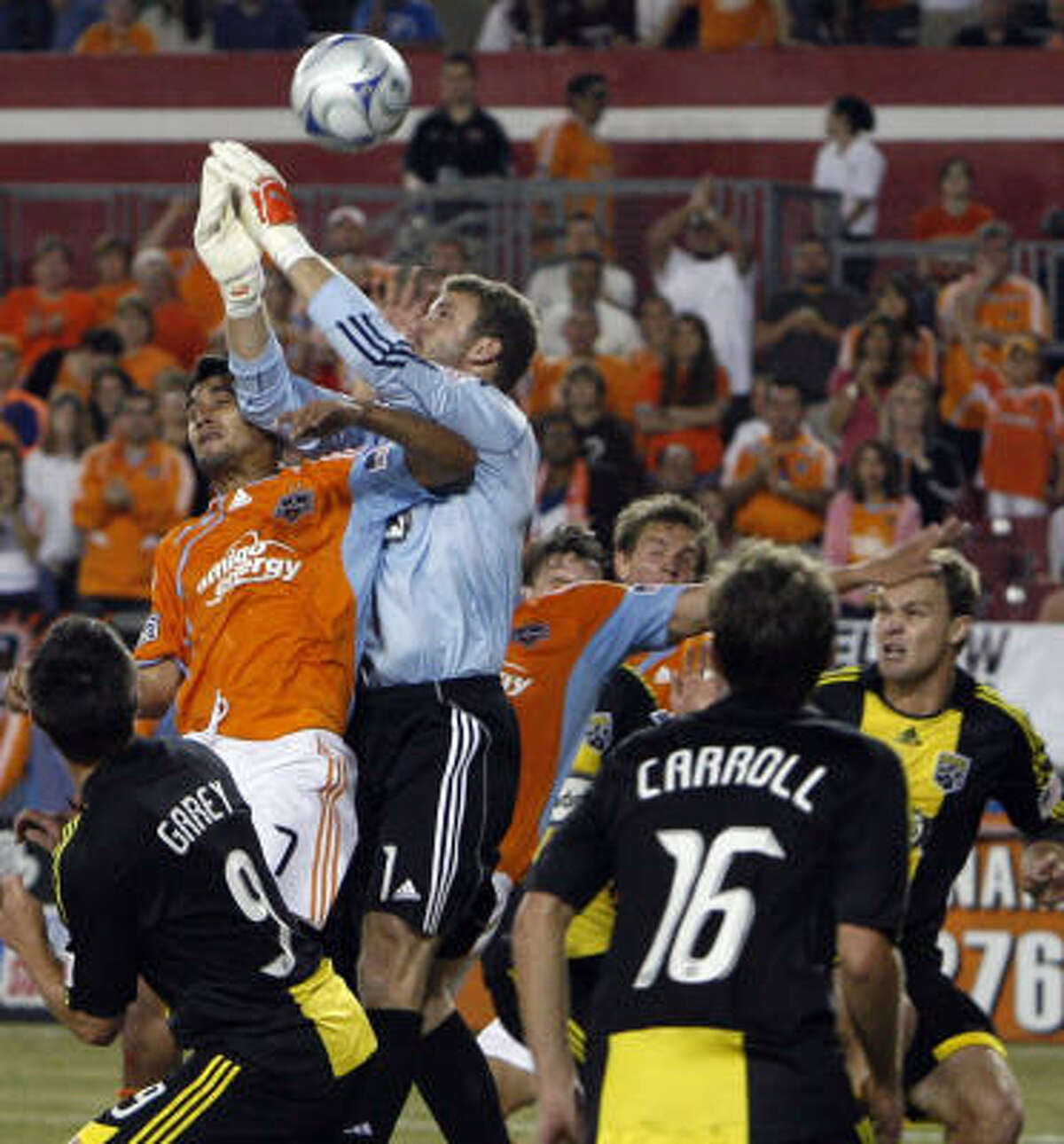 The Dynamo's Chris Wondolowski (#7) battles for the ball against Columbus Crew goalkeeper William Hesmer.