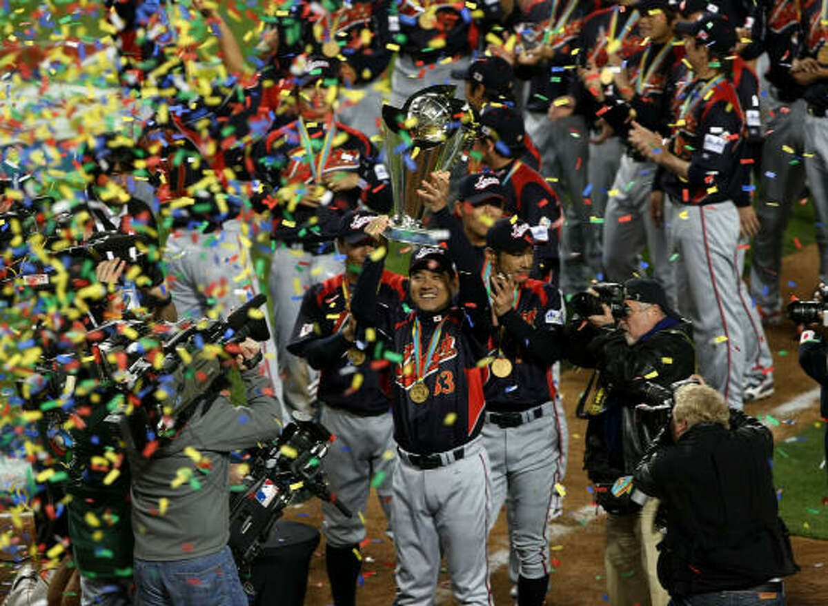 Monday, March 23Finals: Japan 5, Korea 3 (10 inn.): Japanese manager Tatsunori Hara holds up the championship trophy.