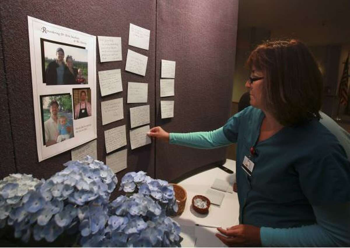 Linda Federico, a pharmacy technician at St. Helena Hospital, places a note at a memorial for Dr. Erin Jacobson and his family on March 23.