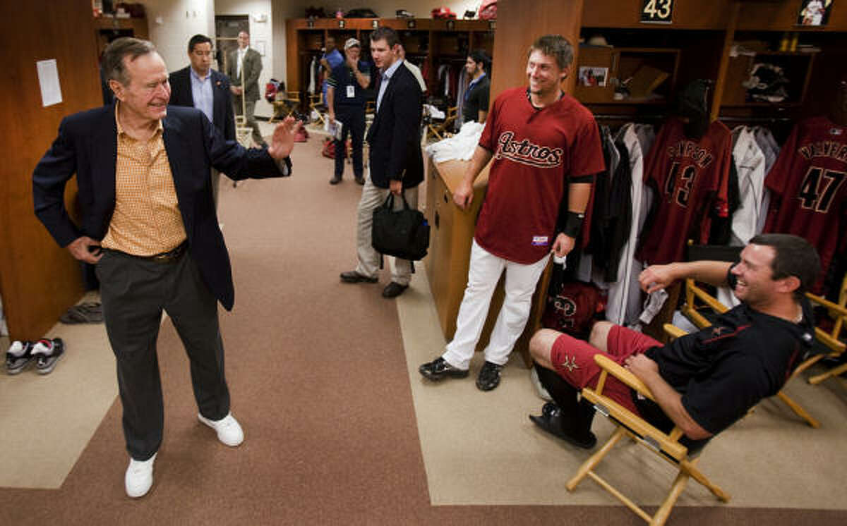 Former President George H.W. Bush waves to Astros players Chris Johnson and Chris Sampson, seated, as Bush tours the Astros clubhouse prior to a spring training game against the Florida Marlins.