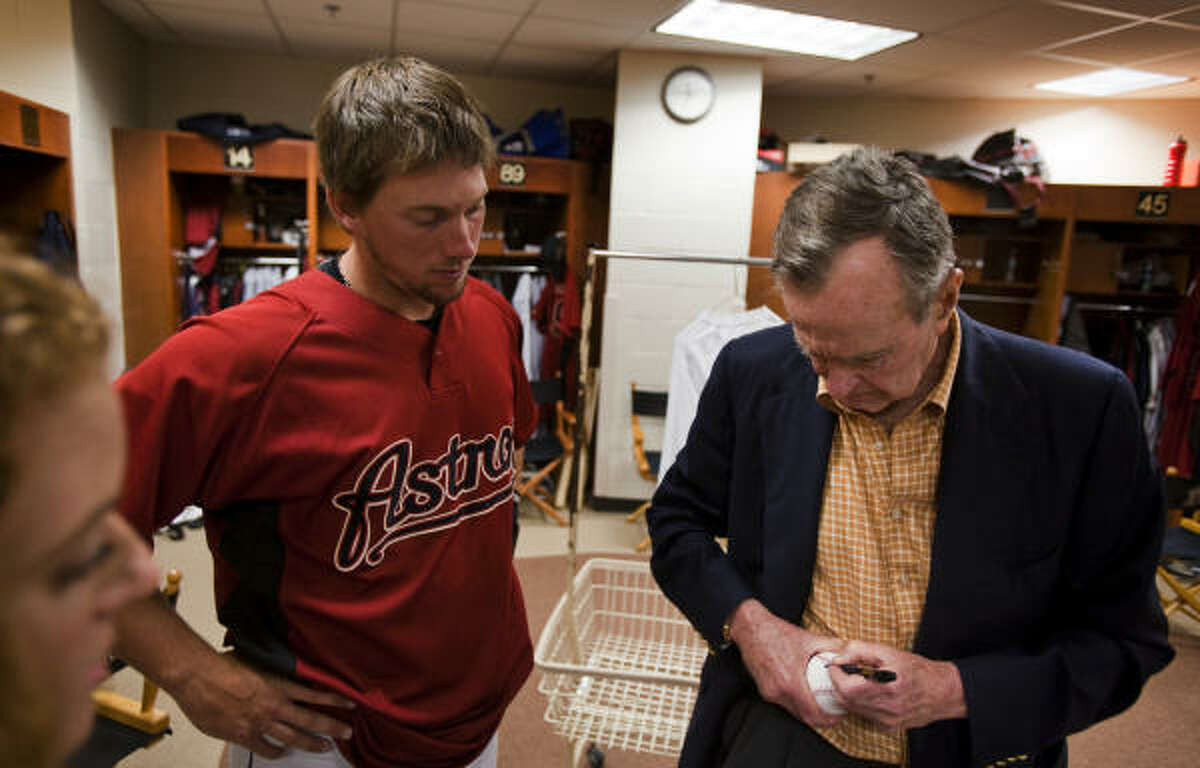 Bush signs an autograph for Astros third baseman Chris Johnson in the clubhouse in Kissimmee, Fla.