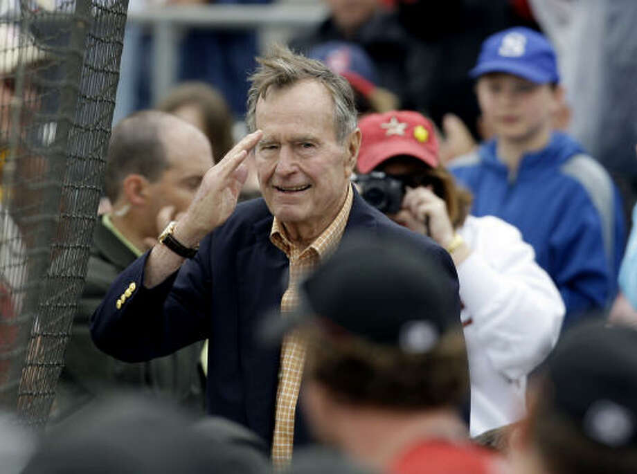 Former President Bush salutes the crowd after being introduced. Photo: Rob Carr, AP