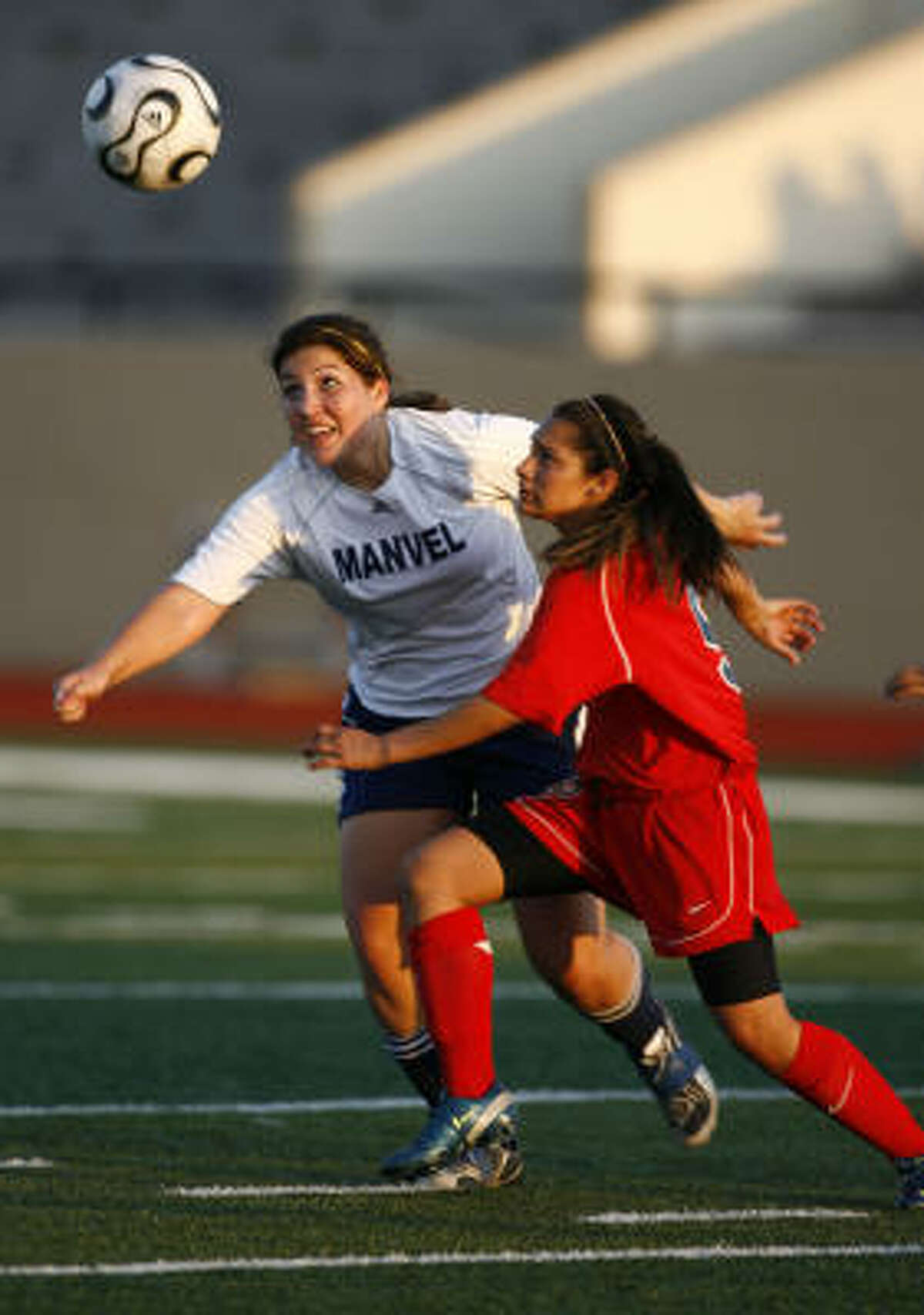 Goose Creek Memorial's Brittany Garza, right, and Manvel's Ellen Smith fight for control of the ball.
