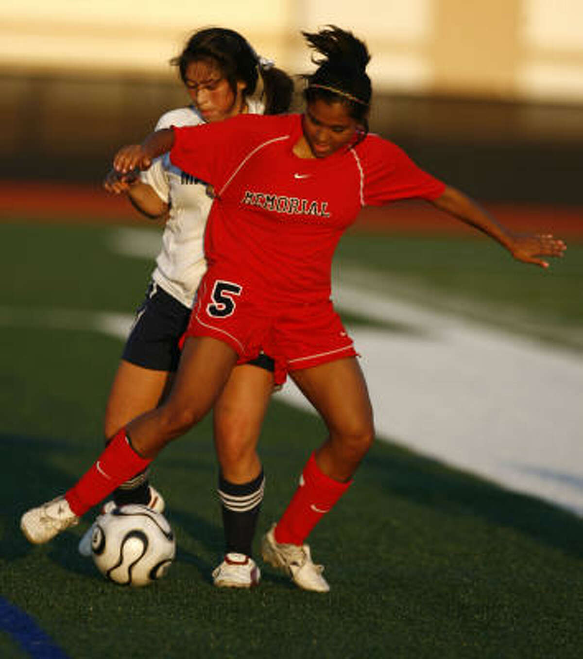 Goose Creek Memorial's Adonika Amador, right, and Manvel's Allyson Martinez fight for control of the ball.