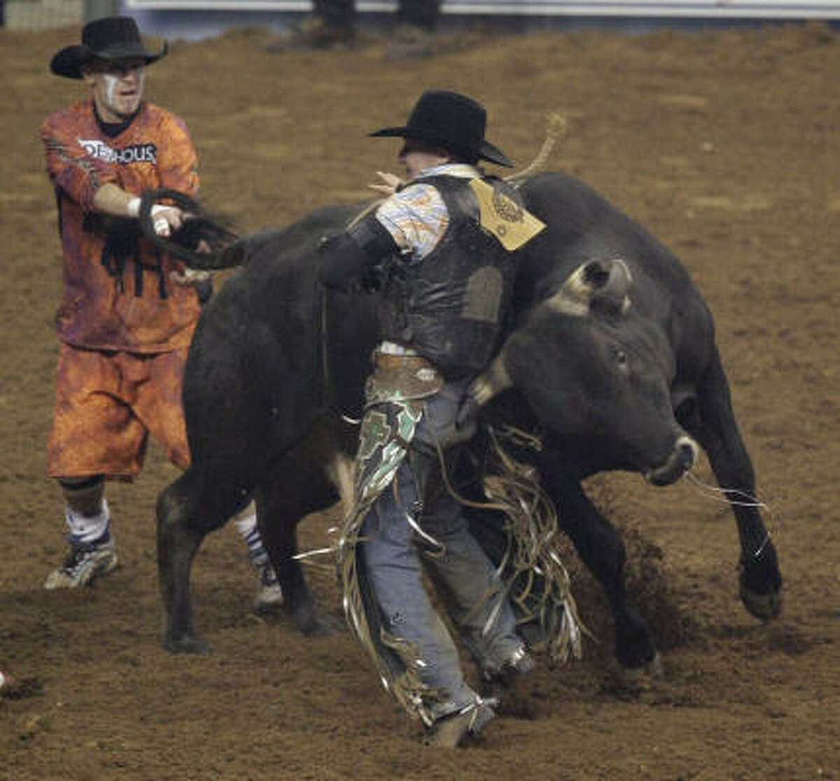 Bullfighter Cory Wall works to untangle Luke Haught after he was bucked off a bull named Razorback during Xtreme Bulls at the Houston Livestock Show and Rodeo.
