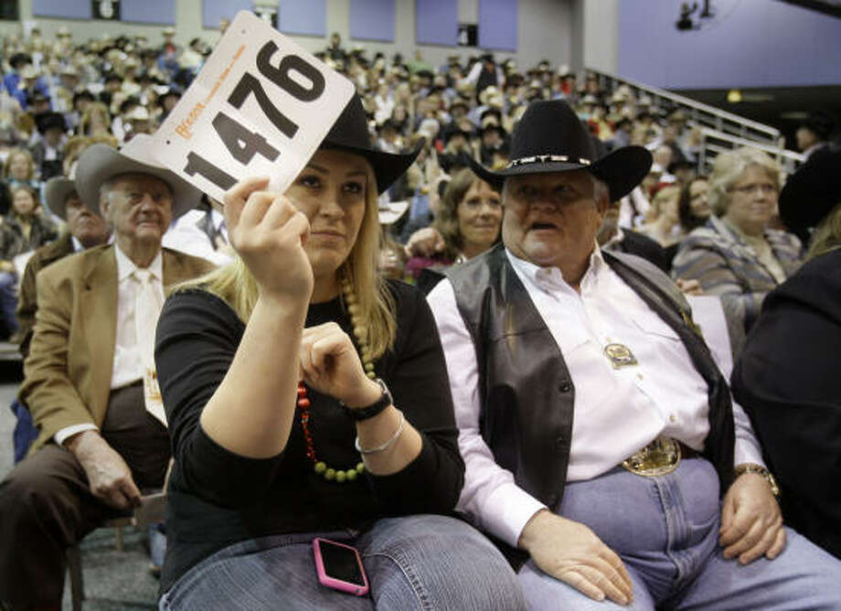 Laura McIngvale daughter of Jim McIngvale owner of Gallery Furniture, bids on the Grand Champion during the Junior Market Steer Auction at Reliant Arena Sales Pavilion at the Houston Livestock Show and Rodeo. She said family friend Dr. Philip Leggett, shown right, helped talk her through the bidding process. Photo: Melissa Phillip, Chronicle