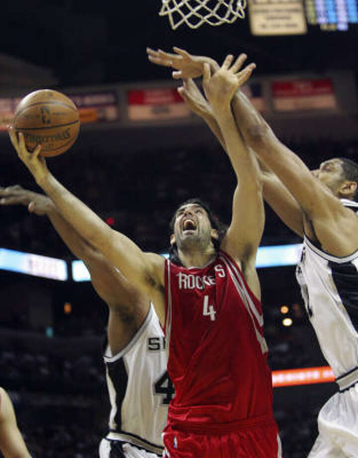 Luis Scola (4) scores inside on Spurs forward Tim Duncan. Photo: Delcia Lopez, AP