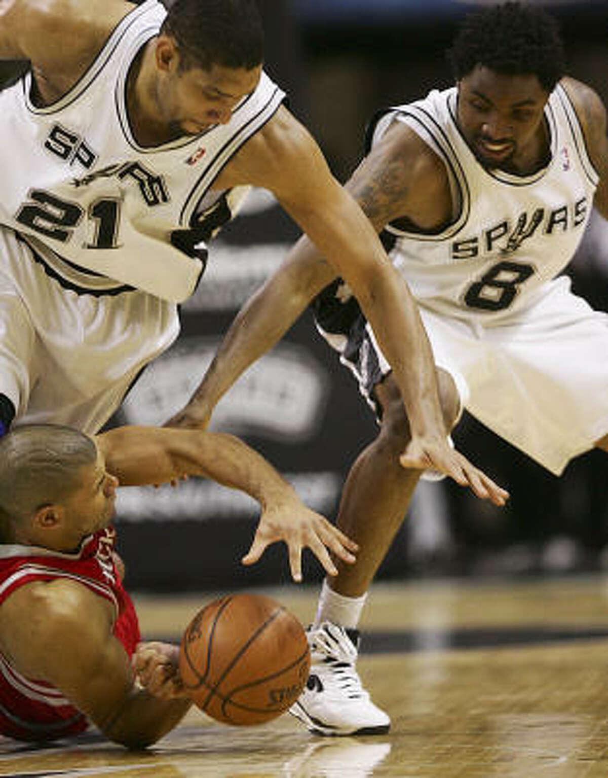 Spurs forward Tim Duncan (21) and Roger Mason Jr. (8) battle Shane Battier for a loose ball.