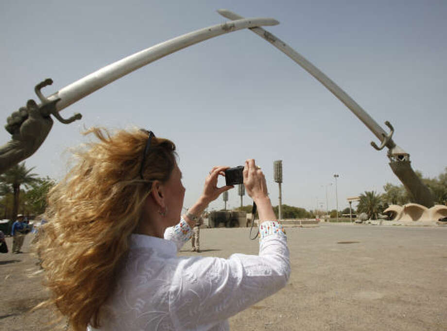 Tina Townsend Greaves, from the U.K., takes a photo of the crossed swords monument in Baghdad's Green Zone on Saturday. Photo: Hadi Mizban, AP