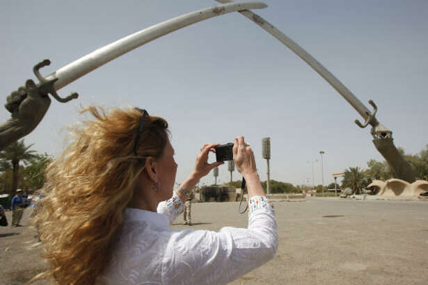 Tina Townsend Greaves, from the U.K., takes a photo of the crossed swords monument in Baghdad's Green Zone on Saturday.