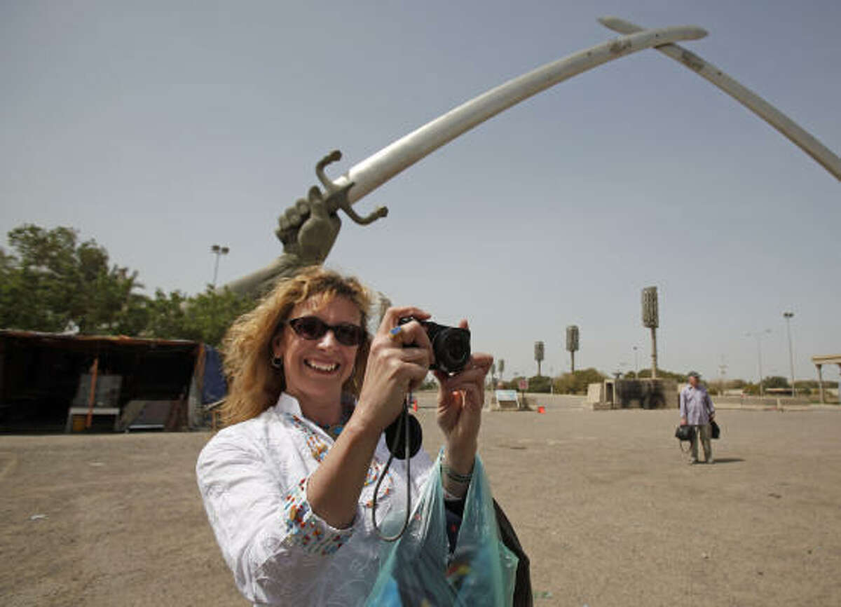 Tina Townsend Greaves, from the U.K., takes a photo during a visit to the crossed swords monument in Baghdad's Green Zone on Saturday.