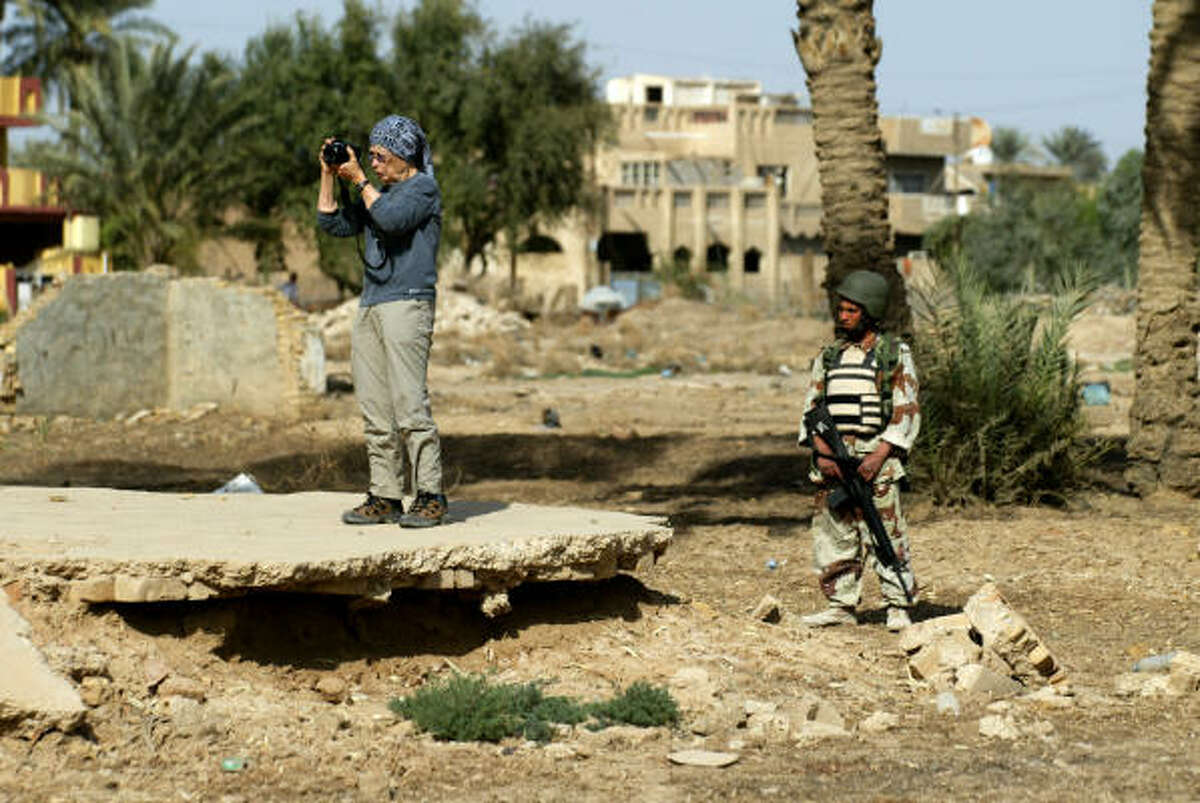 An Iraqi police commando observes as U.S. tourist Jo Rawlins takes pictures of the ruins of the Castle of Persian King Xerxes at Salman Pak south of Baghdad on Saturday.