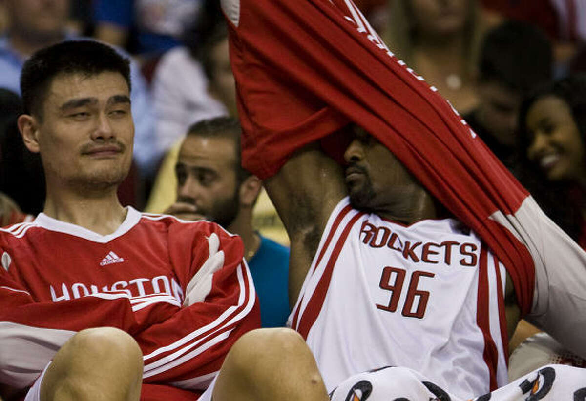 Rockets center Yao Ming, left, and teammate Ron Artest get plenty of rest in the fourth quarter of Friday's rout of the Timberwolves.