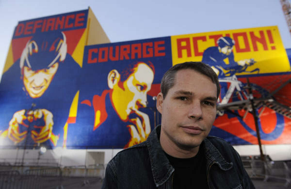 Artist Shepard Fairey poses in front of murals he designed of cyclist Lance Armstrong.