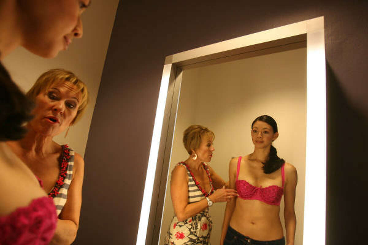 Susan Nethero fits model Marissa Salazar with one of her demi bras in her new store, Intimacy, at the Galleria, May 5.