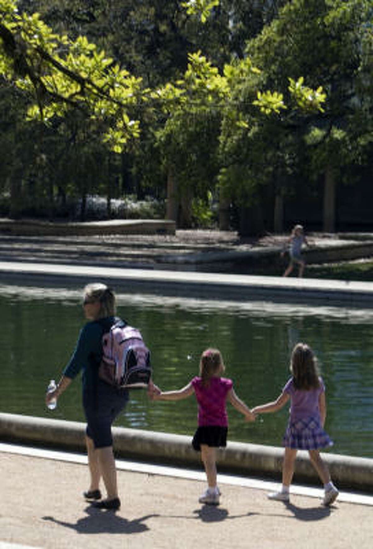 Celebrating their spring break, Stacy Fowle, Leah Hotze, and her mother Kristi Hotze walk to the zoo through Hermann Park.