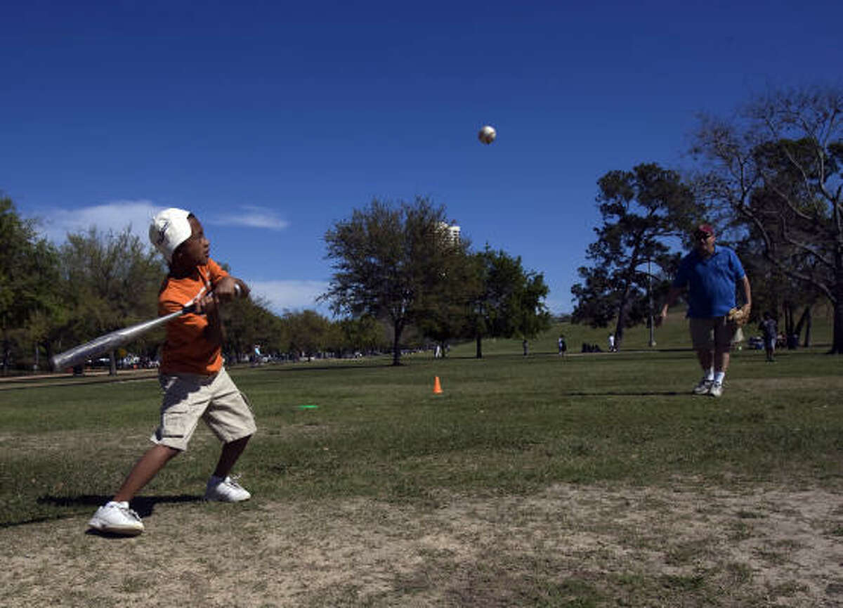 Kevin McKisson pitches to family friend, Nathan Hardrick, in Hermann Park.