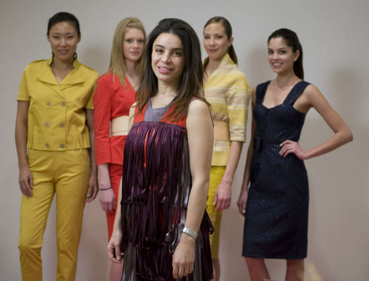 Ports 1961 designer Tia Cibani poses with models wearing her designs at the Neiman Marcus Galleria store.