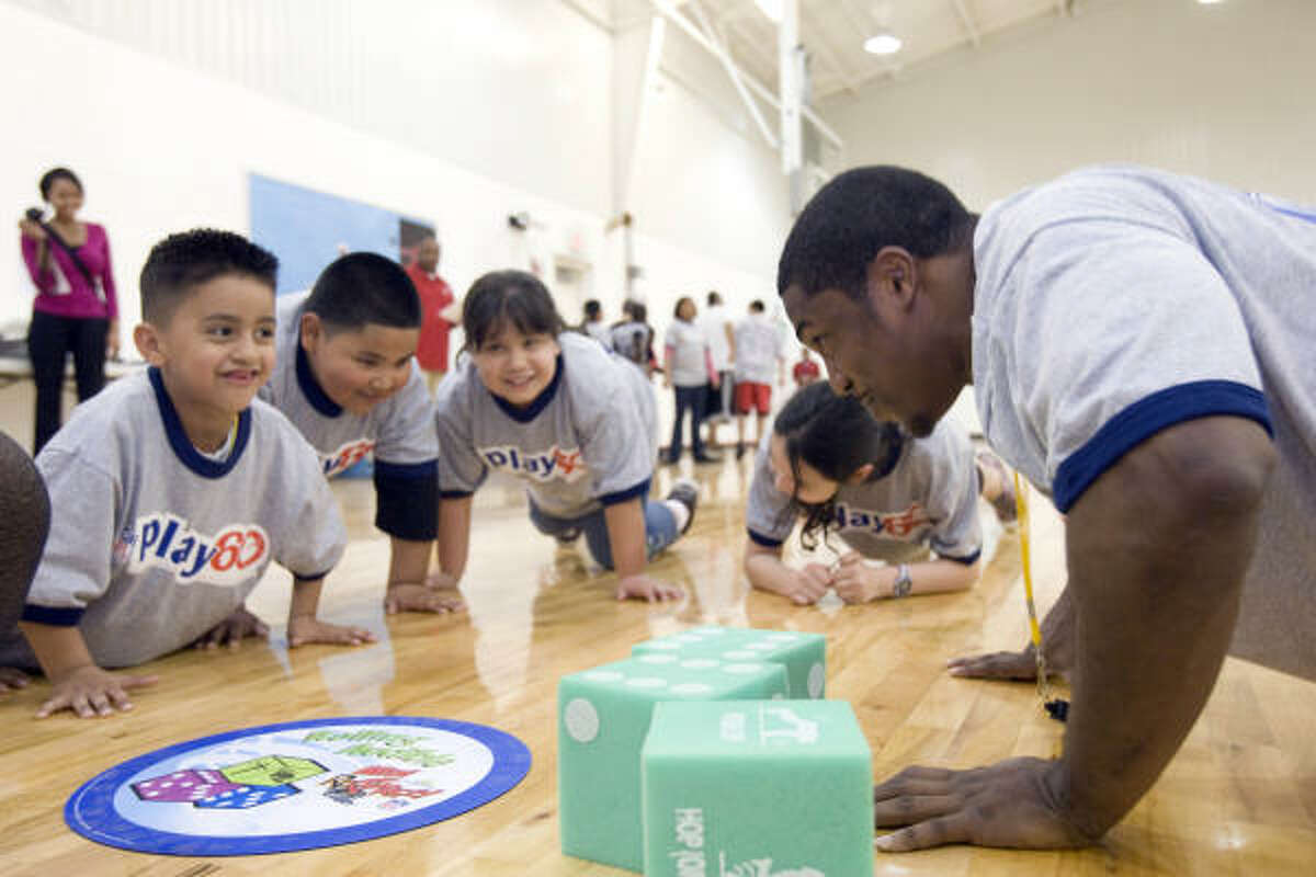 Houston Texans running back Steve Slaton teaches children how to keep fit during a NFL Play 60 event at the Boys & Girls Club of Greater Houston and NFL YET Center in north Houston.