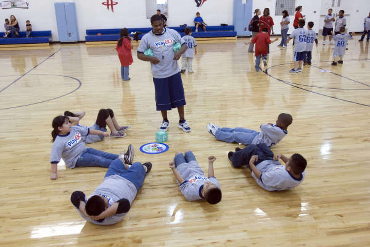 Houston Texans running back Steve Slaton teaches children how to keep fit during a NFL Play 60 event. The purpose of the event was to teach children how to stay active inside and outside of the home.