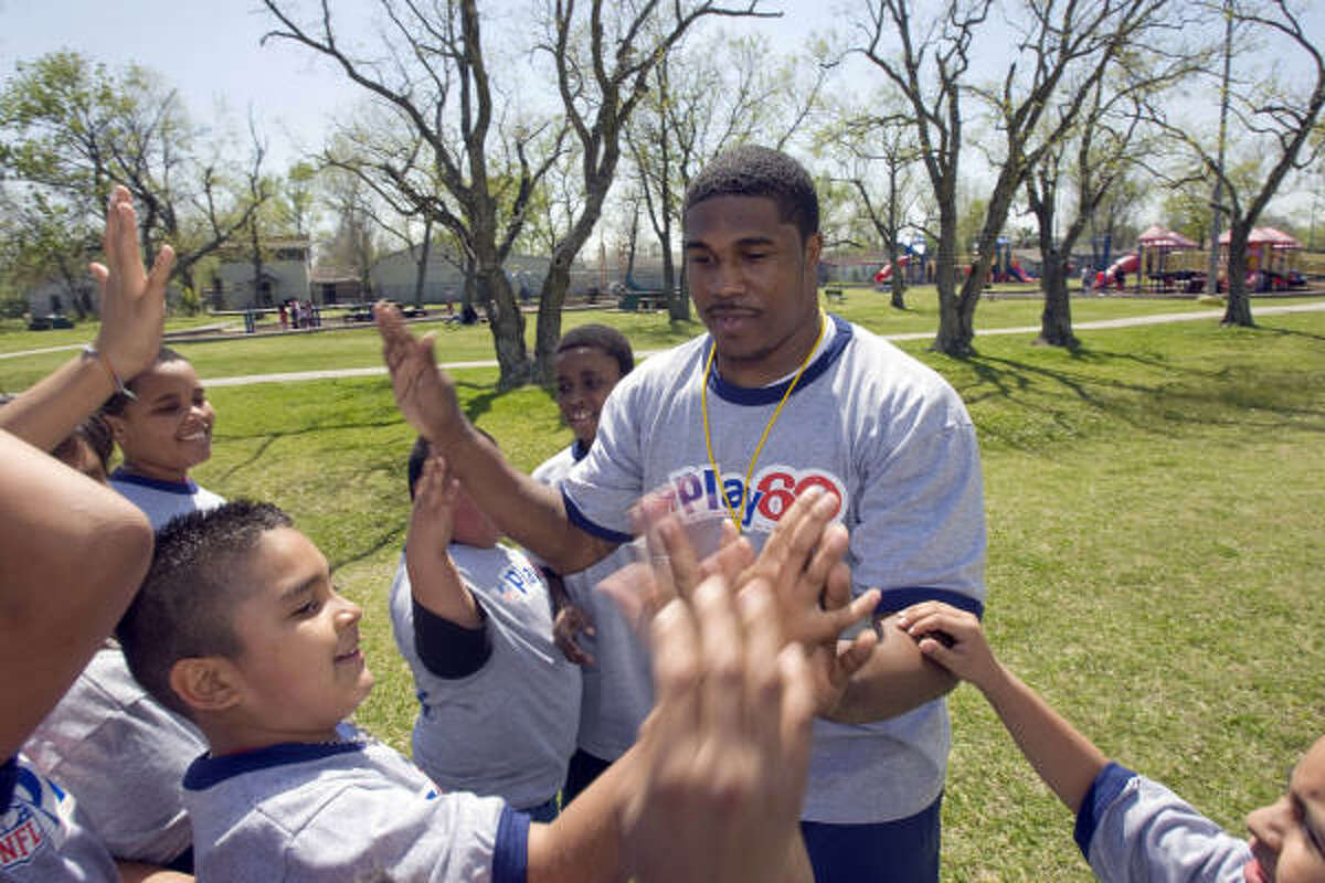 Houston Texans running back Steve Slaton gave high fives after playing a game. More than 50 local children learned different games, drills and how to stretch.