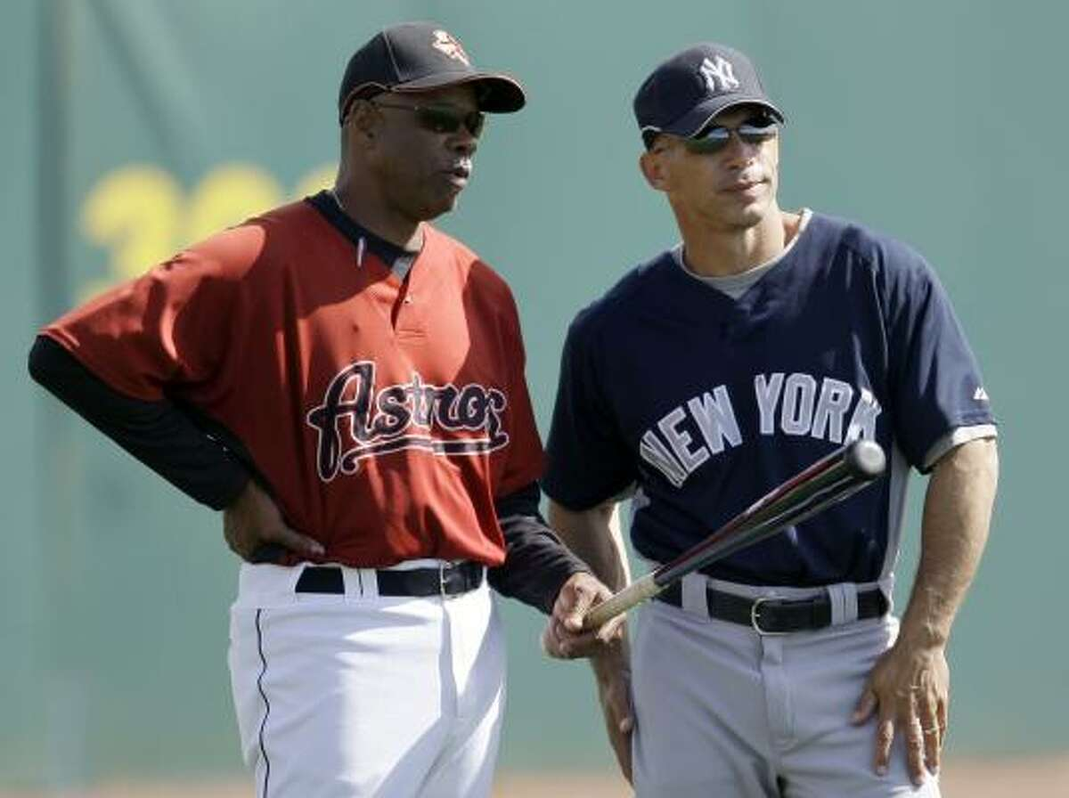 Astros manager Cecil Cooper, left, talks with New York Yankees manager Joe Girardi before their game in Kissimmee, Fla.