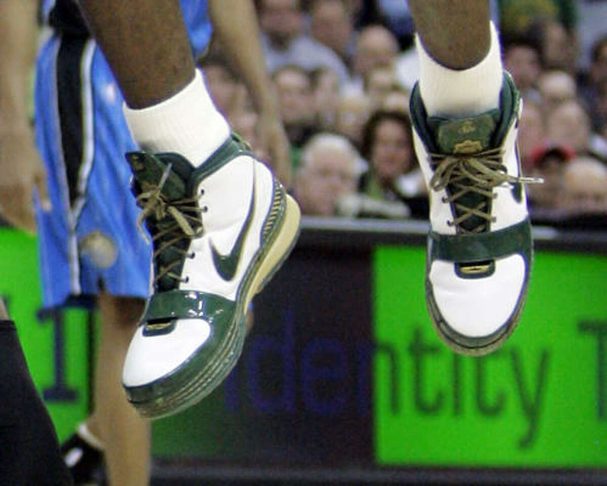 Cleveland Cavaliers' LeBron James shows off his green and white shoes for St. Patrick's Day.