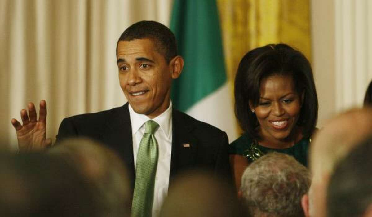 President Barack Obama and first lady Michelle Obama greet guests in the East Room of the White House during a St. Patrick's Day reception.