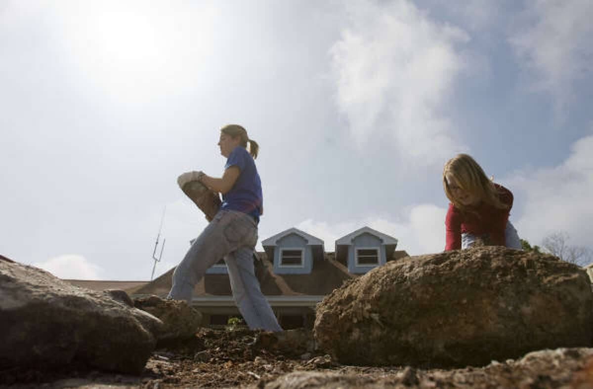 Cara Newton, 11, right, and Skye Snowden, clear debris at a house in Seabrook.