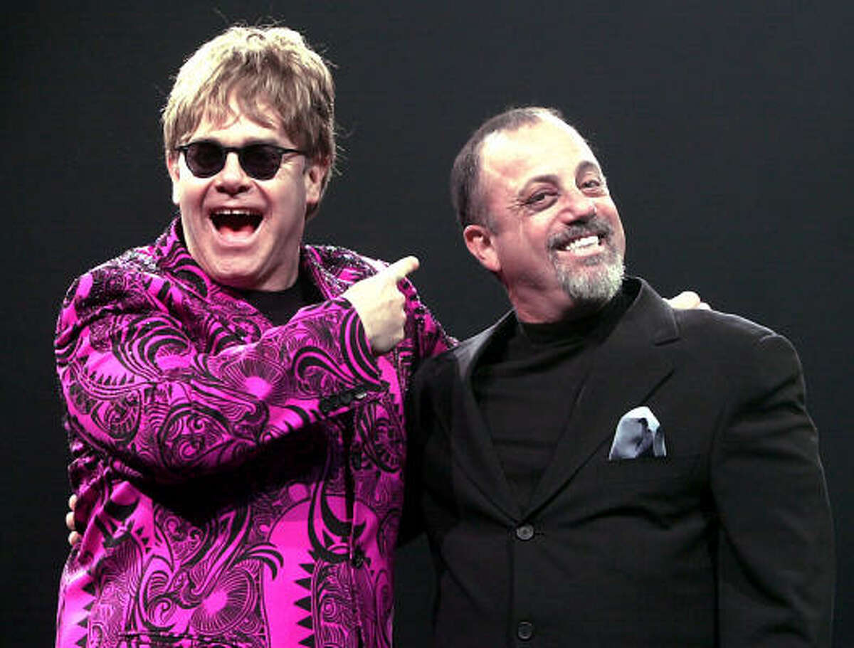 Elton John, left, and Billy Joel joke around for the audience before their concert performance at Kemper Arena in Kansas City, Mo. in 2001.