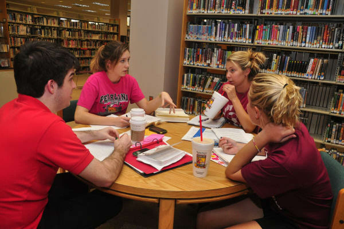 From left, Matthew Elliott, 18, Erin Cunningham, 17, Melanie Smith, 18, and Cathrine Reed, 17 work on a paper at the Pearland Library. It was the library's first day open since Hurricane Ike.