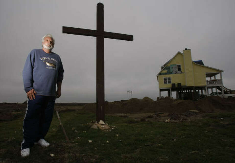 Warren Adams outside of his Gilchrist home near a roadside memorial that was created when a neighbor put up a cross from a local church along Highway 87. Adams' home, while heavily damaged, was the only one in the area left standing. Photo: Julio Cortez, Chronicle