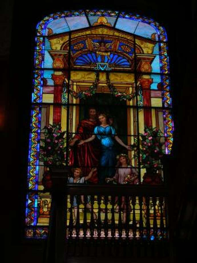 Protective sheeting on the outside of the Moody Mansion helped protect this stained glass artwork. Photo: Mike Madere, Houston Chronicle