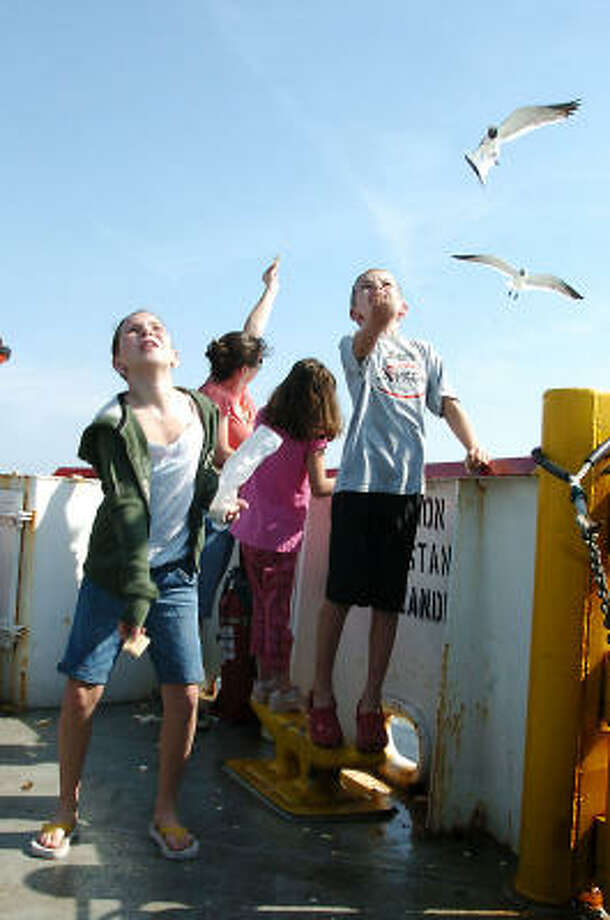 Left to right, Abby Isenhart, 10, and Hunter Isenhart, 8, enjoy feeding the seagulls while riding the Galveston Ferry. Photo: Kirk Sides, For The Chronicle