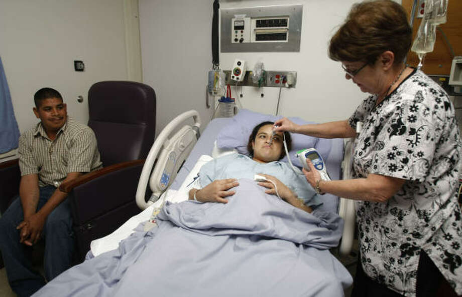 Registered nurse Nancy Johnson, left, checks the temperature of Alicia Maldonado, 23, as Maldonado's husband, Roberto Alvarez, 26, looks on. The Maldonados visited the labor and delivery unit at the University of Texas Medical Branch hospital during a check-up, as Alicia awaits to deliver the couple's second child. Photo: Julio Cortez, Chronicle