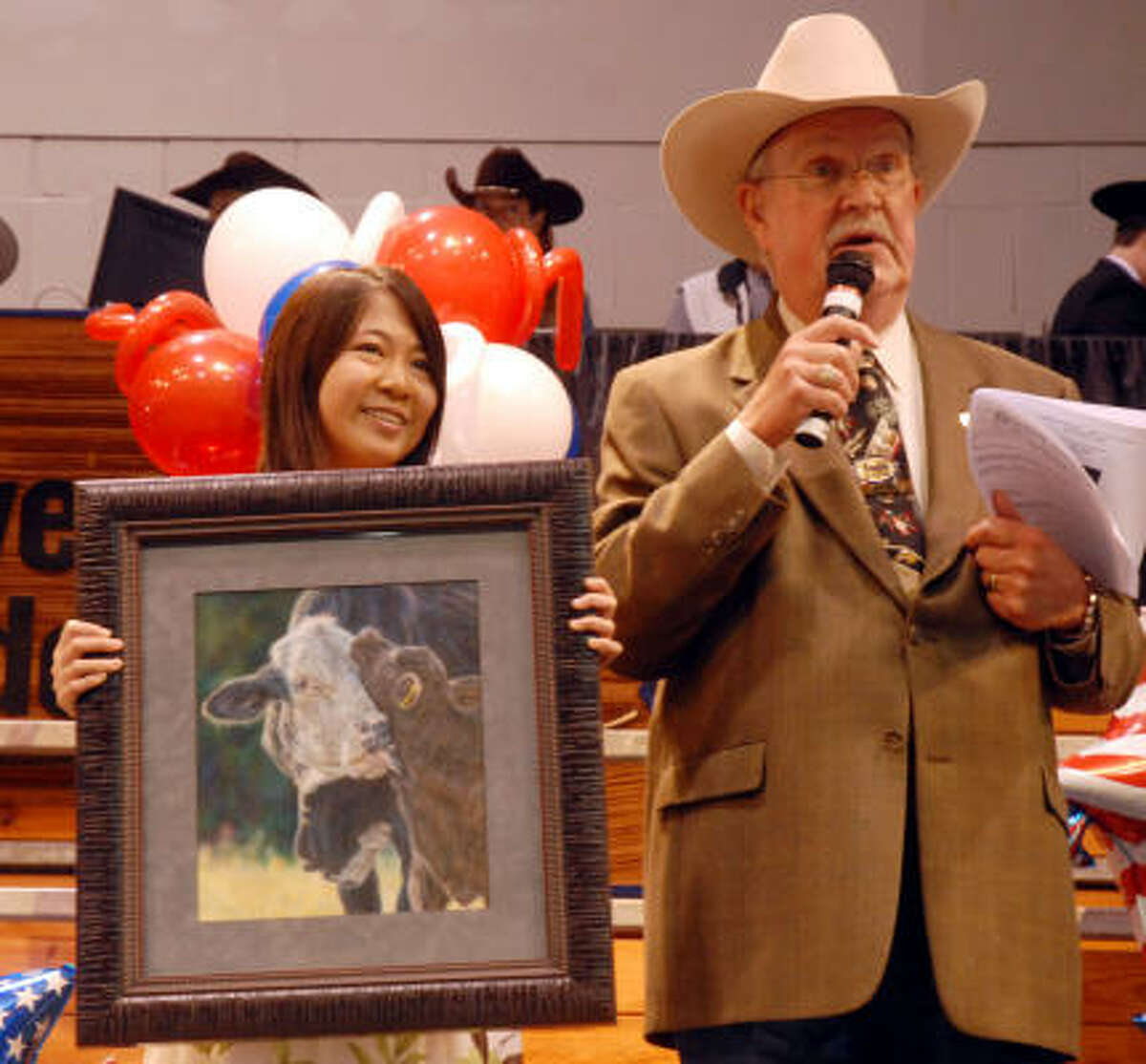 Grand Champion winner Renee Zhan of Katy ISD holds her winning artwork while Constable Bill Bailey talks to the crowd. It sold for $140,000 to Courtney Somerville, Joe Van Matre, Rose Scott and Howard and Donna Webster.
